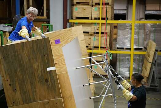 Corning employees prepare glass sheets for finishing. Photo courtesy: Apple