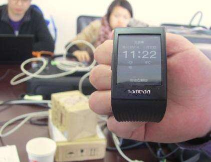 ToMoon's smartwatch, with ToMoon design engineers in the background on site at Ingenic.