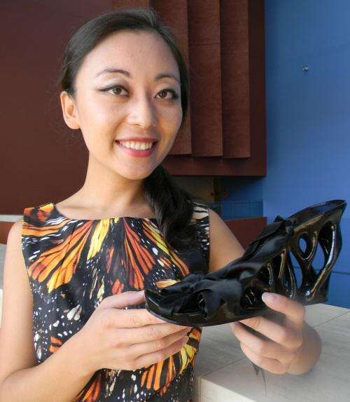 Mary Huang shows a sandal she designed, 3D printed, and wore at the Designers of Things event.