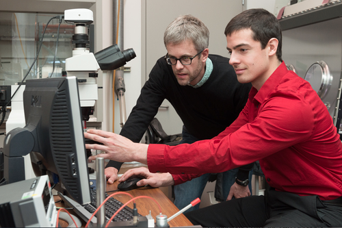 Professor Mike McGehee and doctoral candidate Colin Bailie at Stanford University use a microscope to examine a perovskite solar cell. (Source: Stanford)