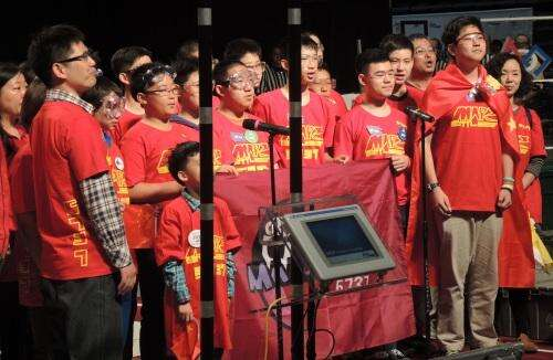 Students from Beijing sing China's national anthem in the opening ceremonies of the event.