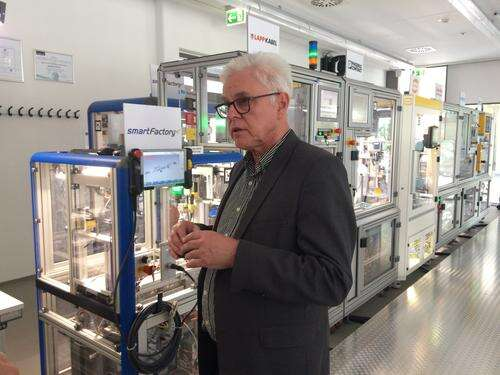 Detlef Zuehlke, director of innovation factory systems at the German Research Center for AI (DFKI) show how the smart factory of the future will use hot-interchangeable modules (background) that can be arranged in any order. (Source: DFKI)